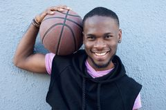 Hombre afroamericano feliz que sonríe con baloncesto Fotografía de archivo