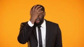 Hombre afroamericano frustrado en el traje de negocios que hace el facepalm, chocado con noticias metrajes