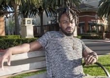Hombre afroamericano hermoso que se sienta en el parque Fotografía de archivo libre de regalías