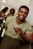Hombre afroamericano holiding una copa de vino en un restaurante Fotografía de archivo