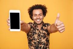 Hombre afroamericano joven alegre que muestra a pantalla en blanco el teléfono móvil Fotografía de archivo