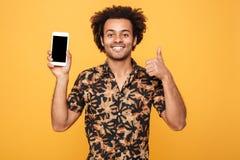 Hombre afroamericano joven alegre que muestra a pantalla en blanco el teléfono móvil Imagen de archivo