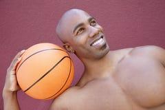 Hombre afroamericano joven con baloncesto en el hombro que mira lejos sobre fondo coloreado Fotos de archivo libres de regalías