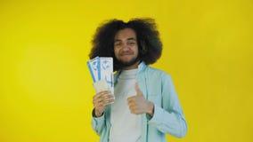 Hombre afroamericano joven con los boletos del documento de embarque en fondo amarillo almacen de video
