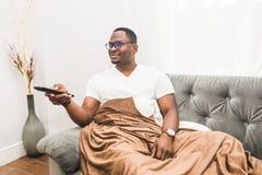 Hombre afroamericano joven, cubierto con una manta, TV de observaci?n en casa foto de archivo