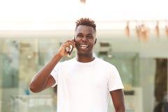 Hombre afroamericano joven de risa que se coloca al aire libre y fabricación de una llamada de teléfono Fotos de archivo libres de regalías