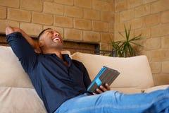 Hombre afroamericano joven de risa que se sienta en el sofá en casa con la tableta imagen de archivo