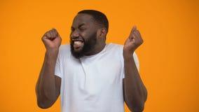 Hombre afroamericano joven extremadamente feliz, ganador de lotería, fondo amarillo almacen de video