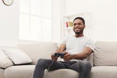 Hombre afroamericano joven feliz en casa que juega a los videojuegos Fotos de archivo libres de regalías
