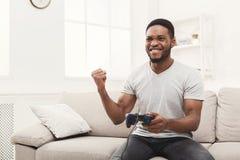 Hombre afroamericano joven feliz en casa que juega los videojuegos y los triunfos Fotografía de archivo libre de regalías