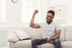 Hombre afroamericano joven feliz en casa que juega los videojuegos y los triunfos Foto de archivo