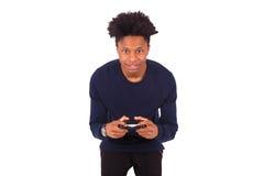 Hombre afroamericano joven feliz que juega a los videojuegos aislados encendido Imagen de archivo