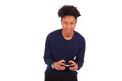 Hombre afroamericano joven feliz que juega a los videojuegos aislados encendido Fotos de archivo