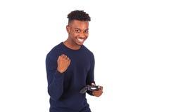 Hombre afroamericano joven feliz que juega a los videojuegos que celebran Fotos de archivo libres de regalías