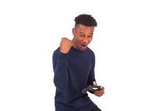 Hombre afroamericano joven feliz que juega a los videojuegos que celebran Foto de archivo