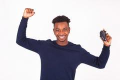 Hombre afroamericano joven feliz que juega a los videojuegos que celebran Foto de archivo libre de regalías