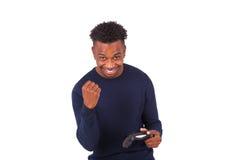 Hombre afroamericano joven feliz que juega a los videojuegos que celebran Imagen de archivo