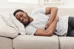Hombre afroamericano joven hermoso que sufre del dolor de estómago fotografía de archivo