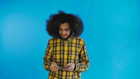 Hombre afroamericano joven que cuenta el dinero del efectivo en fondo azul almacen de metraje de vídeo