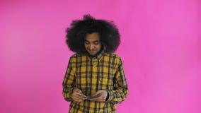 Hombre afroamericano joven que cuenta el dinero del efectivo en fondo púrpura metrajes