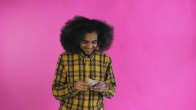 Hombre afroamericano joven que cuenta el dinero del efectivo en fondo p?rpura almacen de video