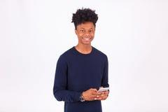 Hombre afroamericano joven que envía un mensaje de texto del SMS en su sma Imagenes de archivo