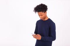 Hombre afroamericano joven que envía un mensaje de texto del SMS en su sma Fotos de archivo