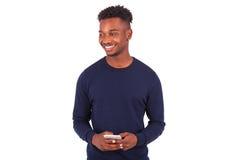 Hombre afroamericano joven que envía un mensaje de texto del SMS en su sma Foto de archivo libre de regalías