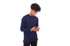 Hombre afroamericano joven que envía un mensaje de texto del SMS en su sma Imágenes de archivo libres de regalías