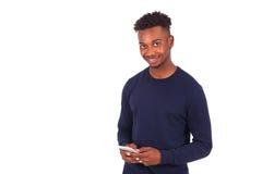 Hombre afroamericano joven que envía un mensaje de texto del SMS en su sma Fotografía de archivo