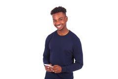 Hombre afroamericano joven que envía un mensaje de texto del SMS en su sma Fotografía de archivo libre de regalías