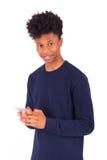 Hombre afroamericano joven que envía un mensaje de texto del SMS en su sma Imagen de archivo libre de regalías