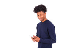 Hombre afroamericano joven que envía un mensaje de texto del SMS en su sma Imagen de archivo