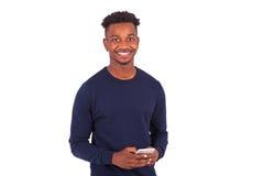 Hombre afroamericano joven que envía un mensaje de texto del SMS en su smartphone Imagenes de archivo