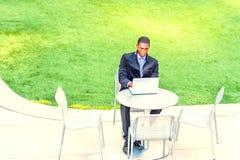 Hombre afroamericano joven que estudia en el ordenador portátil en el verde Imagen de archivo