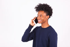 Hombre afroamericano joven que hace una llamada de teléfono en su smartphone Foto de archivo libre de regalías