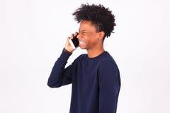 Hombre afroamericano joven que hace una llamada de teléfono en su smartphone Fotos de archivo libres de regalías
