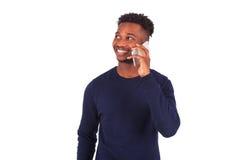 Hombre afroamericano joven que hace una llamada de teléfono en su smartphone Imagen de archivo libre de regalías
