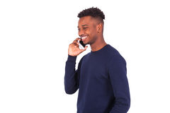 Hombre afroamericano joven que hace una llamada de teléfono en su smartphone Fotografía de archivo libre de regalías
