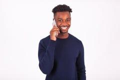 Hombre afroamericano joven que hace una llamada de teléfono en su smartphone Fotografía de archivo