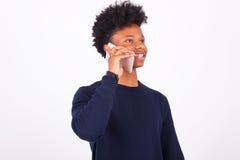 Hombre afroamericano joven que hace una llamada de teléfono en su smartphone Foto de archivo