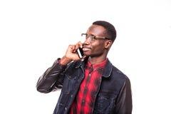 Hombre afroamericano joven que hace una llamada de teléfono en su smartphone en blanco Fotografía de archivo