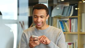 Hombre afroamericano joven que hojea en línea en Smartphone metrajes