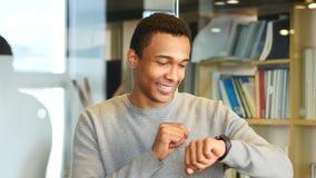 Hombre afroamericano joven que hojea en línea en Smartwatch almacen de video
