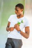 Hombre afroamericano joven que le falta con la rosa del blanco en nuevo Yo Imagenes de archivo