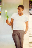 Hombre afroamericano joven que le falta con la rosa del blanco en nuevo Yo Imágenes de archivo libres de regalías