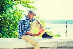 Hombre afroamericano joven que lee el libro rojo, relajación al aire libre adentro Imagen de archivo