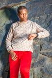 Hombre afroamericano joven que mira el reloj, para Yo que espera fotos de archivo