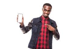 Hombre afroamericano joven que señala su pantalla del smartphone en el fondo blanco Imágenes de archivo libres de regalías