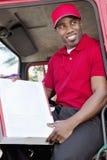 Hombre afroamericano joven que se sienta en camión de reparto con la caja imagen de archivo libre de regalías